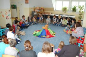 einen Eltern-Kind-Gruppe sitzt in einem Kreis