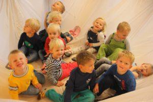 Mehrere Kinder sitzen zusammen und lachen