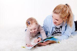 Sprechen lernen: Eine Mutter liest mit ihrer Tochter ein Bilderbuch