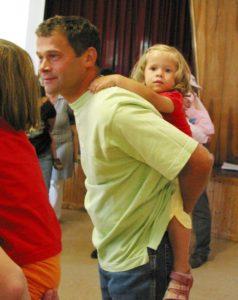 Ein Vater trägt seine Tochter Huckepack