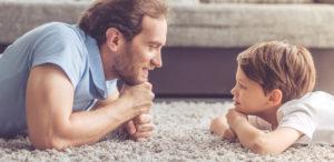 Achtsamkeit: Vater und Sohn liegen gemeinsam auf dem Boden