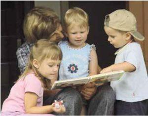 Mutter mit ihren drei Kindern beim Vorlesen