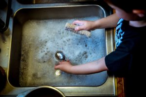 Ein kleines Kind hilft beim Geschirr Abwaschen