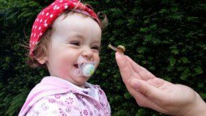 Eine erwachsene Person zeigt einem Kleinkind eine Schnecke