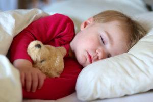 Kind mit Teddybär beim Einschlafen