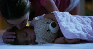 Mutter küsst ihren Sohn beim Einschlafen