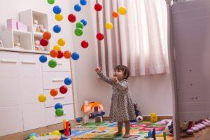Kleines Mädchen spielt mit Bällen