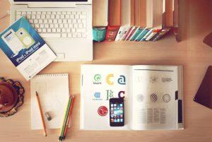 Ein organisierter Arbeitsplatz auf dem ein Laptop, ein Notizbuch und ein Schulbuch zu sehen sind